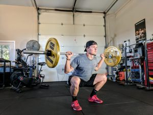 man lifting barbell in his garage converted into gym