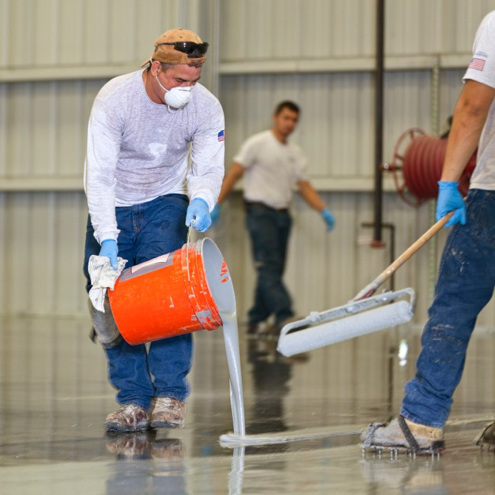 men applying and installing epoxy on flooring